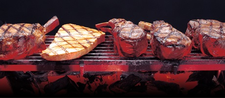 Steaks and chops cooking on a broiler grill