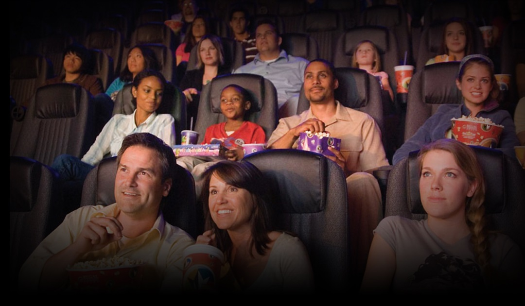 Guests enjoying a film in a stadium seating movie theater