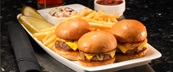 Three sliders with cheese and onions served with french fries, pickle spears and dipping sauces